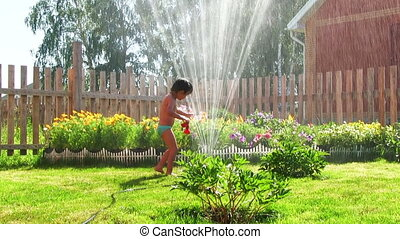 Boy plays with water - Little boy plays with sprinkler, in...