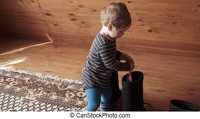 Boy plays with woolen boots