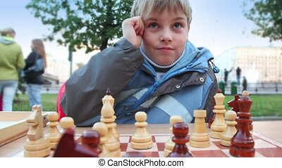 Boy plays wooden chess in park, people walk around