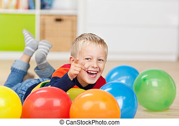 Portrait of happy little boy pointing while lying with colorful balloons on floor