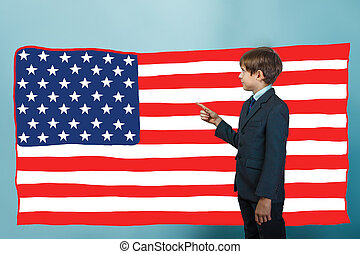 boy points his finger at the American flag