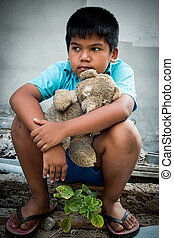 Boy poor with old teddy bear sitting on old wood pile