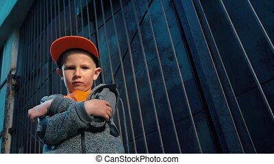 Boy posing on camera standing in a back street, crossing his arms in front of him