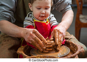 boy potter at work in the studio. two years old - boy potter...