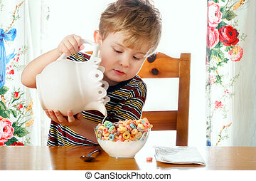 A young boy holding a pitcher pours milk into his cereal bowl.