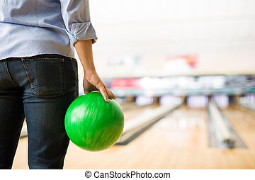 Boy Practicing Bowling With Green Ball In Club