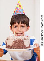 Boy presenting birthday cake