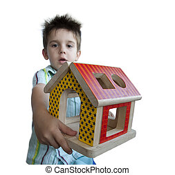 Boy presenting wood colorful house toy. White isolated