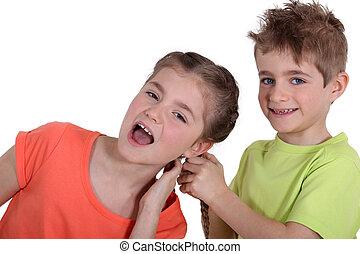 Boy pulling girl's hair