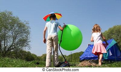 Boy pumps rubber ball, little girl goes inside tent