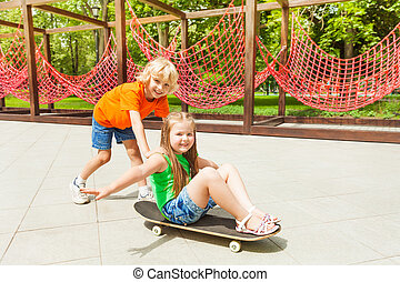 Boy pushes girl on skateboard with arms apart
