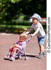 Boy pushing sister in a stroller