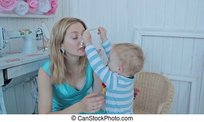 Boy put on necklace to mother