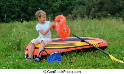 boy puts on a life jacket sitting on an inflatable rubber...