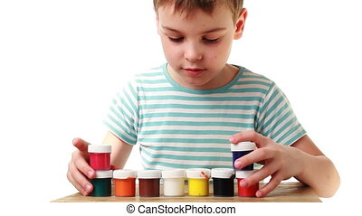 boy puts pyramid of cups with different colors on white background