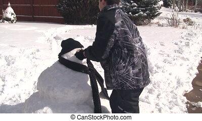 Boy putting face on snowman