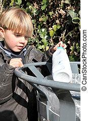 Boy putting rubbish in a park bin