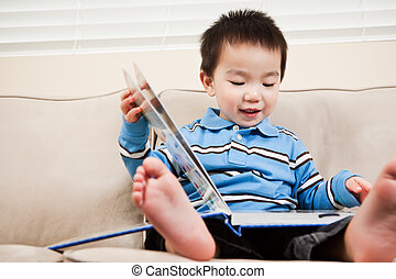 Boy reading a book - A portrait of an asian boy reading a...