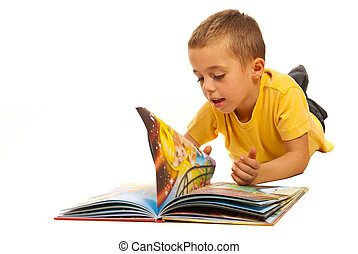 Boy reading a book - Happy boy lying on floor and reading a...