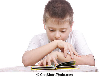 Boy reading book at table