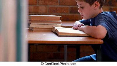 Boy reading book in classroom - Little boy reading book in...