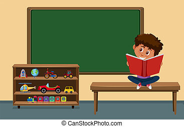 Boy reading book in the classroom