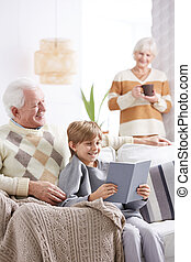 Boy reading book with grandfather