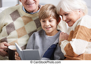 Boy reading book with grandparents