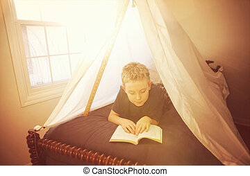 Boy reading in a fort made of sheets