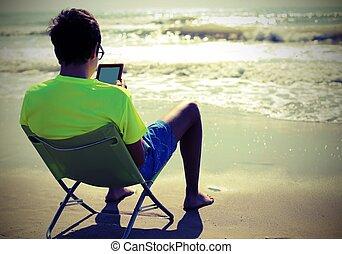 boy reads ebook on the beach chair in summer