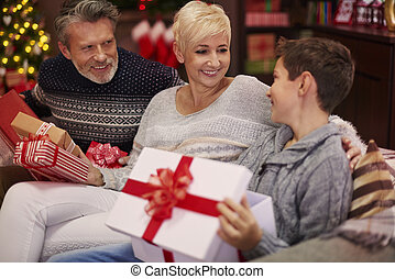 Boy receiving a gift from his parents