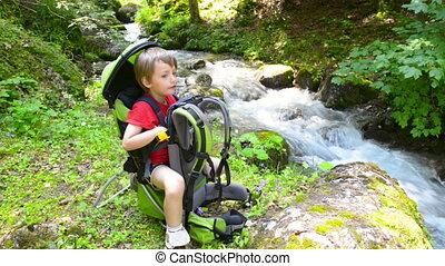 Boy relaxing in a kid carrier near river