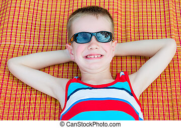 Boy resting on the beach, top view