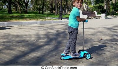 Boy rides a scooter in the park.