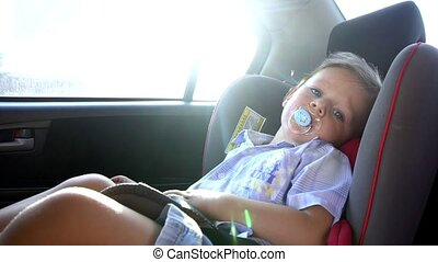 Boy rides in a child's car seat