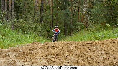 Boy riding a bike in the forest.