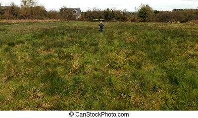 Boy riding a bike in the green field 4k