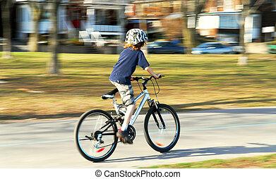 Boy riding a bike - Panning shot of a boy riding a bicycle,...