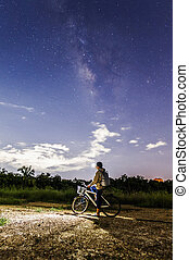 boy riding a bike with the Milky Way as a backdrop
