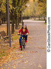 Happy boy riding a bycicle in autumn park