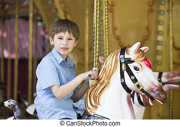 Boy riding a retro carousel in the form of a horse