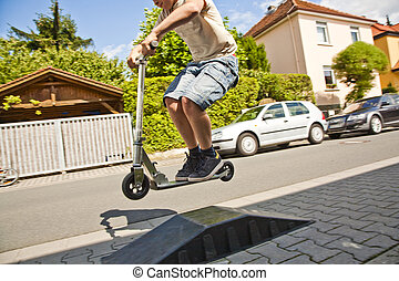 boy riding a scooter going airborne at a sidewalk