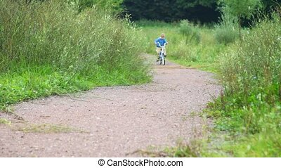 boy riding bicycle in park, to camera