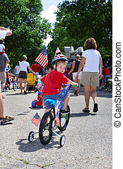 Boy riding his bike in a neighborhood 4th of July parade - A...