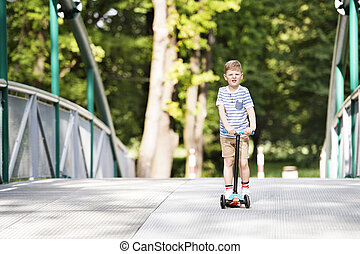 Boy riding his scooter in the local park. Sunny summer.