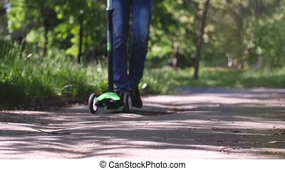Boy riding mini kick scooter and his young brother running in the park in slow motion. Happy childhood. 1920x1080