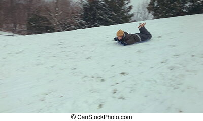 Boy riding on sleds in winter snow