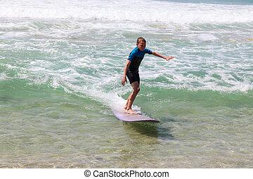 Boy riding wave on purple longboard at the beach.