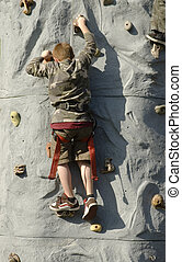 Boy rock climbing - Boy climbing on an artificial rock...