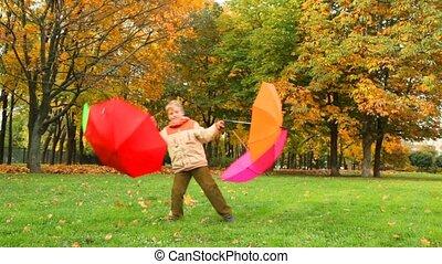 boy rotates with four umbrellas in autumn park